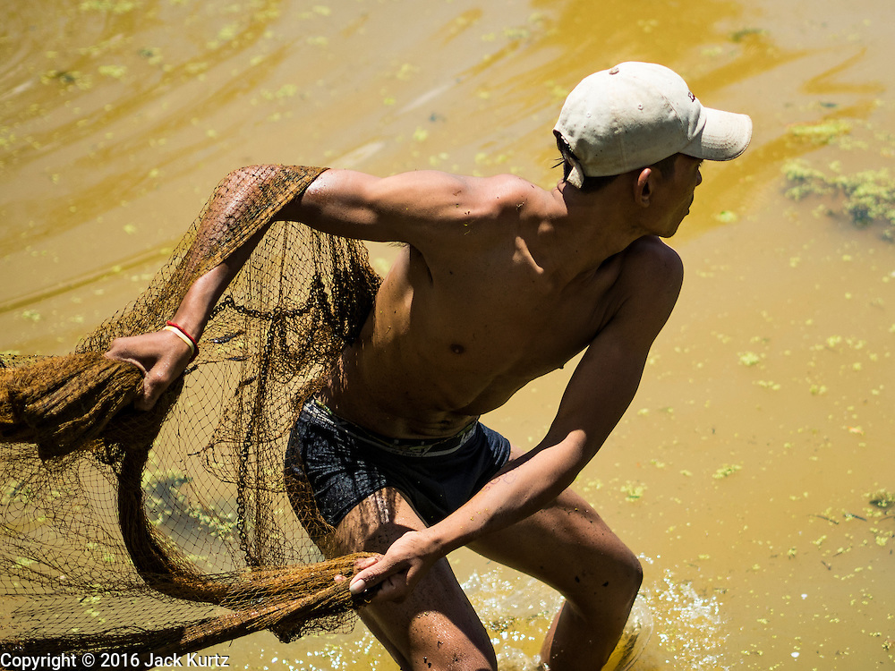 31 MAY 2016 - SIEM REAP, CAMBODIA: A man doing subsistence fishing throws a fishing net into the Siem Reap River in Siem Reap, Cambodia.      PHOTO BY JACK KURTZ