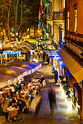 Busy outdoor restaurant at night, Rome, Italy.