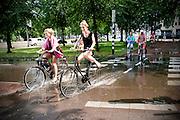 Twee meisjes fietsen door een diepe plas water die na noodweer in Utrecht is ontstaan