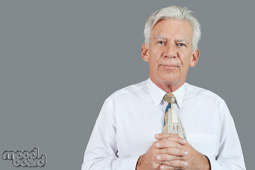 Portrait of senior businessman with hands clasped over gray background
