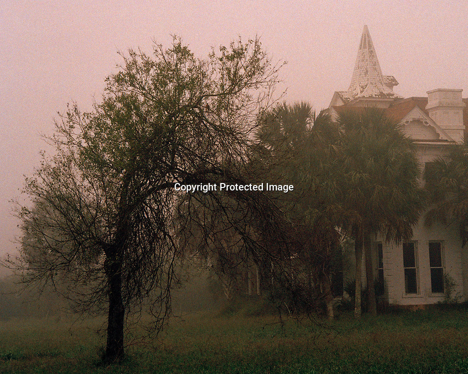 "Large abandoned house in evening fog in Brownsville, Texas. NOTE: Click ""Shopping Cart"" icon for available sizes and prices. If a ""Purchase this image"" screen opens, click arrow on it. Doing so does not constitute making a purchase. To purchase, additional steps are required."