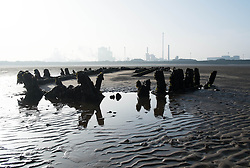 © Licensed to London News Pictures. 13/03/2014<br /> <br /> South Gare, Teesside, England, UK<br /> <br /> The wooden remnants of a ship wreck are visible as they lie in the sand at low tide in an area known as South Gare at the mouth of the River Tees on Teesside.<br /> <br /> Photo credit : Ian Forsyth/LNP