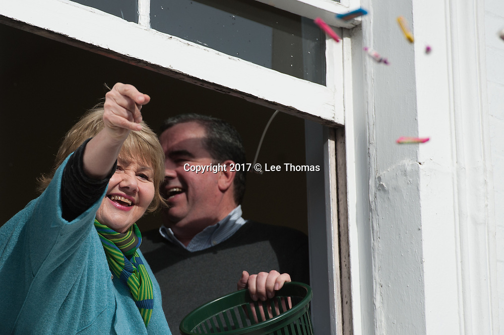 "Atherstone, Warwickshire, UK. 28th February 2017. Pictured:  Eastenders star Annette Badland, throws sweets to children in the streets prior to the beginning of the Ball Game. / Hundreds of people of all ages flood into the Warwickshire town of Atherstone to either participate or watch the infamous Atherstone Ball Game. The event is being held for the 818th time opening when this year's celebrity, Eastenders star Annette Badland, throws the ball into the crowd of people. The Atherstone Ball Game is an ancient Shrove Tuesday tradition in which the people of this rural North Warwickshire town awaken and literally brawl over a large ball up and down the town's small ancient streets. Shops are boarded up, local schools are closed and towns people of Atherstone gather in the main street at 3pm with only one rule in mind, the ball cannot be taken outside the town. Anything and everything else goes. The winner in this no holds barred contest is the person holding onto the ball at 5pm. This traditional Shrove Tuesday Ball Game has been held annually since the early 12th Century and is one of Atherstone's claims to fame. The origin of the game, in the reign of King John, is thought to have been a ""Match of Gold that was played between the Warwickshire Lads and the Leicestershire Lads on Shrove Tuesday"".  // Lee Thomas, Tel. 07784142973. Email: leepthomas@gmail.com  www.leept.co.uk (0000635435)"