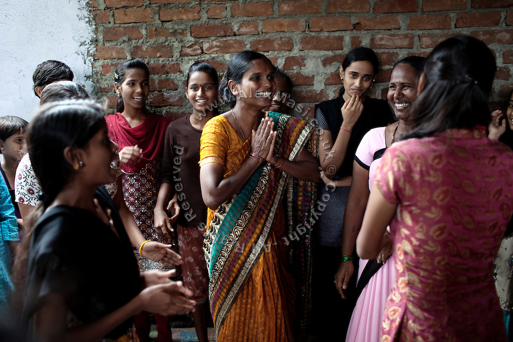 Anita Suresh Kasbe, 41, the Unicef community facilitator is greeting the girls attending the Unicef-run 'Deepshikha Prerika' project inside the Milind Nagar Pipeline Area, an urban slum on the outskirts of Mumbai, Maharashtra, India. Here, Mayuri Mahesh Pandit, 13, (behind the facilitator) she resides with her family.