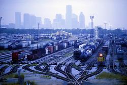 Rail yard with downtown Houston skyline in background.