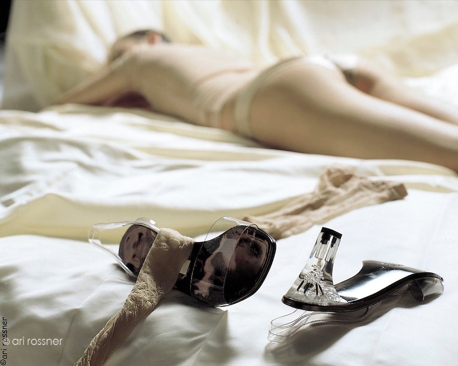 woman in lingerie lying on a bed - her transparent heel shoes and stockings thrown aside