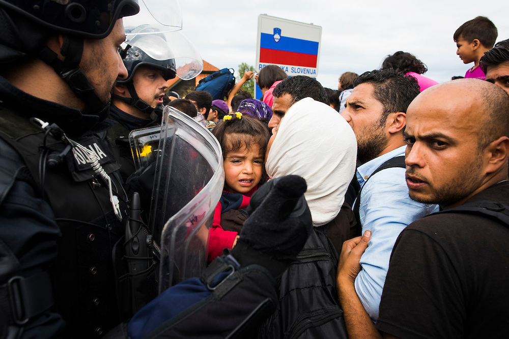 Migrants push against police in riot gear at the Slovenian border on September 19, 2015 in Harmonica, Croatia.