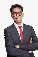 Portrait of young Asian businessman with arms crossed against white background
