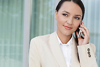 Beautiful businesswoman answering cell phone outdoors