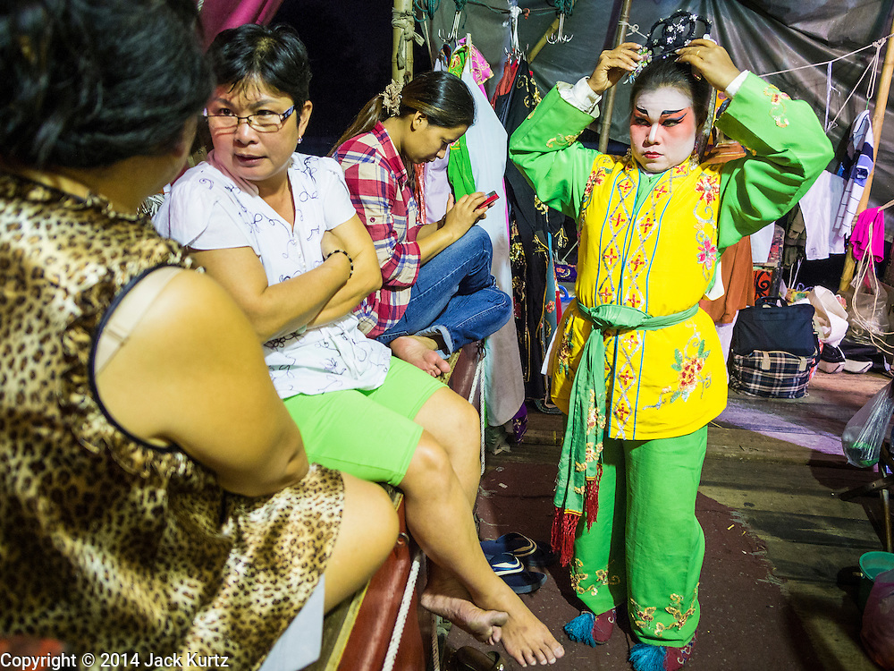 "28 JANUARY 2014 - BANGKOK, THAILAND: A performer with the Tear Kia Ee Lye Heng opera troupe puts on her costume before a show. They were performing for a business in the Min Buri district of Bangkok for the Lunar New Year, which this year is Jan 31. Chinese opera was once very popular in Thailand, where it is called ""Ngiew."" It is usually performed in the Teochew language. Millions of Teochew speaking Chinese emigrated to Thailand (then Siam) in the 18th and 19th centuries and brought their cultural practices with them. Recently the popularity of ngiew has faded as people turn to performances of opera on DVD or movies. There are still as many 30 Chinese opera troupes left in Bangkok and its environs. They are especially busy during Chinese New Year when they travel from Chinese temple to Chinese temple performing on stages they put up in streets near the temple, sometimes sleeping on hammocks they sling under their stage. They are also frequently hired by Chinese owned businesses to perform as a form of merit making.    PHOTO BY JACK KURTZ"