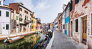 "In Burano, houses are brightly painted blue, red, orange, and yellow along a fishermen's boat canal. Burano, known for knitted lacework, fishing, and colorfully painted houses, is a small archipelago of four islands linked by bridges in the Venetian Lagoon, in the Veneto region of Italy, Europe. Burano's traditional house colors are strictly regulated by government. The Romans may have been first to settle Burano. Romantic Venice (Venezia), ""City of Canals,"" stretches across 100+ small islands in the marshy Venetian Lagoon along the Adriatic Sea in northeast Italy, between the mouths of the Po and Piave Rivers. Venice and the Venetian Lagoon are honored on UNESCO's World Heritage List. This panorama was stitched from 6 overlapping photos."
