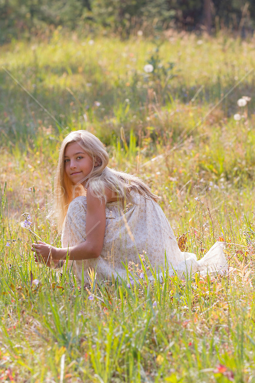 young girl picking wild flowers in a field