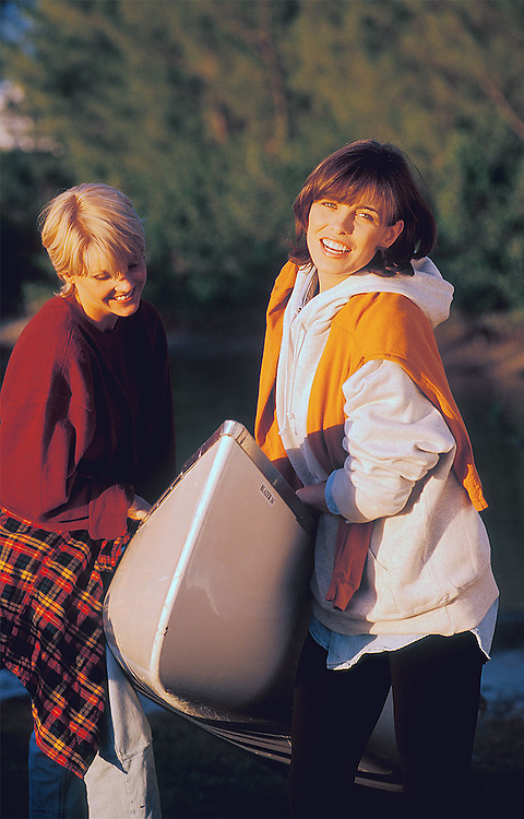 Two young women bring a canoe out of water.