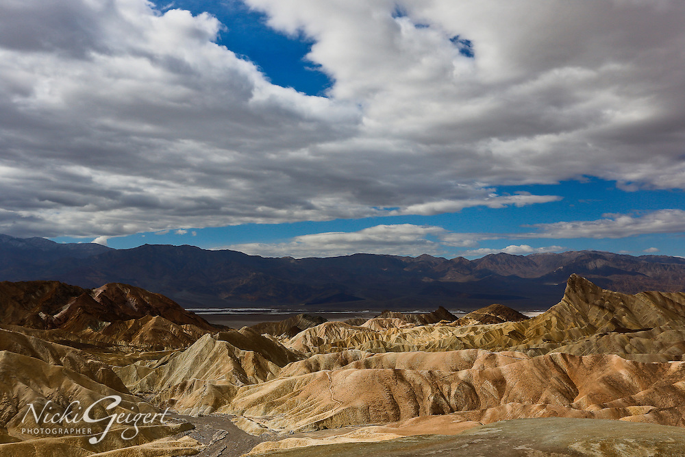 Desert landscape, eroded sandstone, distant mountains, wide cloudy blue sky, Death Valley. Landscape and nature photography wall art. Stock image