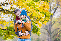 Portrait of mature beautiful woman showing pictures on camera while her husband is hugging her from behind in park