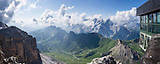 A lift from Passo Pordoi up to Sass Pordoi in the Sella Group gives a sweeping view of Dolomites peaks including their highest, glacier-clad Marmolada (3343 meters / 10,968 feet), Italy. From Pordoi Pass on state highway 48 (Grand Strader delle Dolomiti), take the rapid cable car ascent or hike up to the restaurant on Sass Pordoi at 2952m. Pordoi Pass (or Pordoijoch, 2239 meters/7346 feet) is the highest surfaced road traversing a pass in the Dolomites. On the Padon chain in the foreground (a ridge of volcanic origin carpeted with lush green pasture and wildflowers), we highly recommend hiking the Bindelweg/Viel del Pan trail starting from Pordoi Pass. The Dolomites are part of the Southern Limestone Alps, Europe. UNESCO honored the Dolomites as a natural World Heritage Site in 2009. This panorama was stitched from 3 overlapping photos.