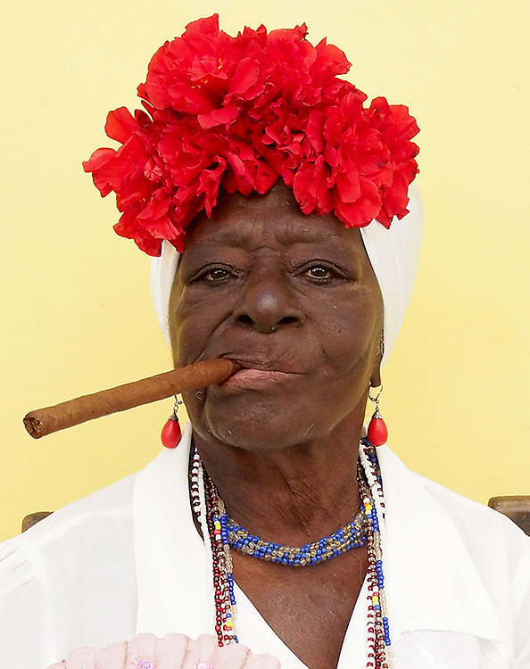 Cuban Lady sits with her cuban cigar in traditional clothes in Old Havana, Cuba Cuba Travel images from Havana Cuba. Pictures by Chris Pavlich Photography.