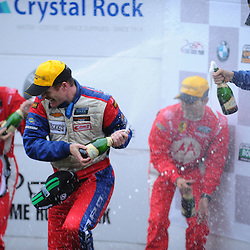 Stevenson Motorsports Chevrolet Camaro driver Robin Liddell (second from left) retreats from a champaign spray while he and teammate John Edwards (far right) celebrate their victory in the Grand-Am Rolex Sports Car Series Championship Race at Lime Rock Park in Lakeville, Conn.