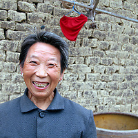 Asia, China, Yichang. Farm woman with welcoming smile in rural China.