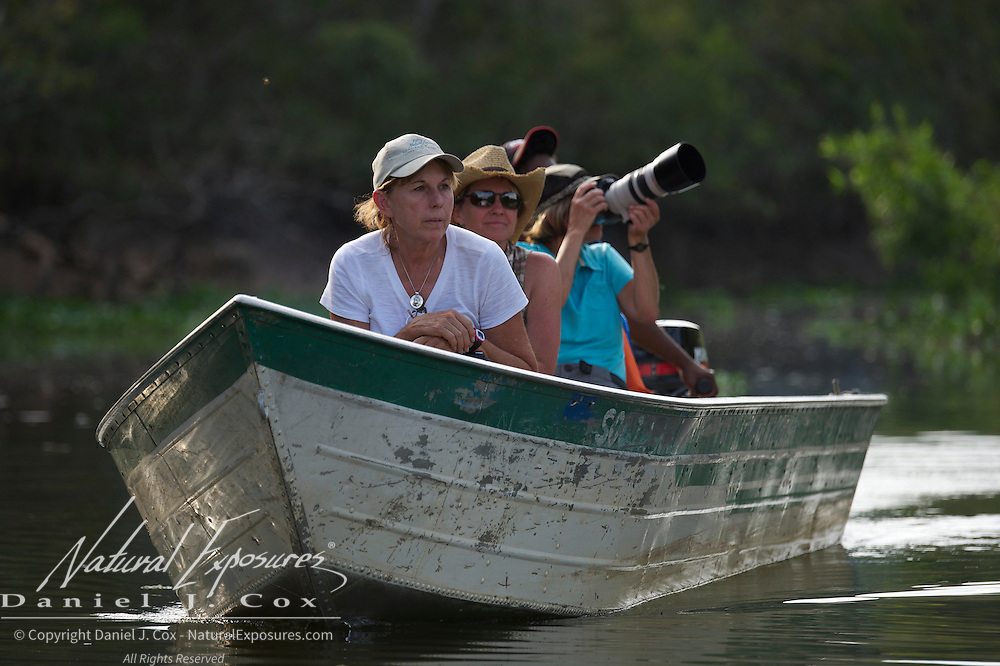 Tourists in small boat on the Cuiaba River searching for jaguars. Pantanal, Brazil.