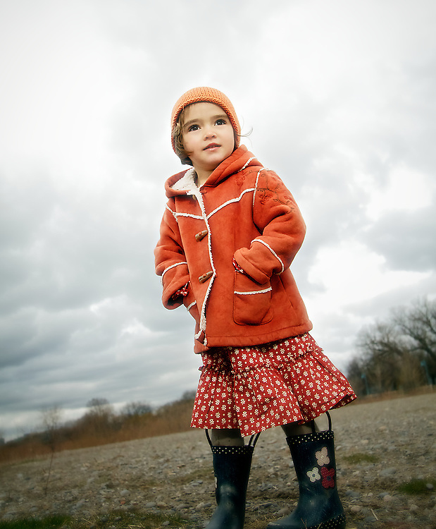 Autumn portrait of girl wearing red hat and coat, hands jammed in pockets.