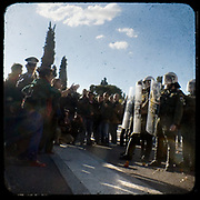 Teenagers confronting riot police in front of the Greek parliament. <br /> <br /> Following the murder of a 15 year old boy, Alexandros Grigoropoulos, by a policeman on 6 December 2008 widespread riots, protests and unrest followed lasting for several weeks and spreading beyond the capital and even overseas<br /> <br /> When I walked in the streets of my town the day after the riots I instantly forgot the image I had about Athens, that of a bustling, peaceful, energetic metropolis and in my mind came the old photographs from WWII, the civil war and the students uprising against the dictatorship. <br /> <br /> Thus I decided not to turn my digital camera straight to the destroyed buildings but to photograph through an old camera that worked as a filter, a barrier between me and the city.