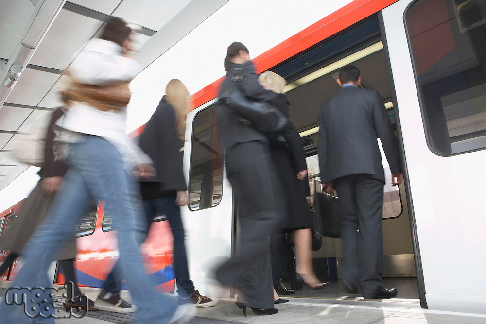Business Commuters Getting on Train motion blur low angle view