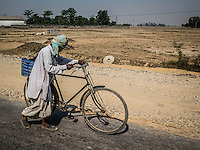 Man walking along the road with his bike on the road from Bardia National Park to Nepalgunj, Nepal.