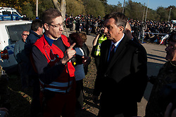 Licensed to London News Pictures. 24/10/2015. Rigonce, Slovenia. Migrants are waiting to be escorted to the camps in Dobovo and Brezice, Slovenia. President of Slovenia Borut Pahor (right) is visiting the camp in Rigonce and talkin to the Red cross. Photo: Marko Vanovsek/LNP
