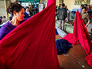 "22 DECEMBER 2017 - HANOI, VIETNAM:  Workers unfurl bolts of red fabric in the wholesale clothes and fabric section of Dong Xuan Market in the old quarter of Hanoi. The old quarter is the heart of Hanoi, with narrow streets and lots of small shops but it's being ""gentrified"" because of tourism and some of the shops are being turned into hotels and cafes for tourists and wealthy Vietnamese.   PHOTO BY JACK KURTZ"