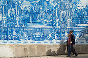 People passing Azulejos Portuguese blue and white wall tiles of Capela das Almas de Santa Catarina  - St Catherine's Chapel in Porto, Portugal