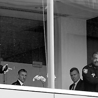 (Boston, MA - 1/20/15) Boston Police, including Commissioner William Evans, second from left, and Superintendent-in-Chief William Gross, right, are seen through a second floor window at Brigham and Women's Hospital following the shooting of a doctor, Tuesday, January 20, 2015. Staff photo by Angela Rowlings.