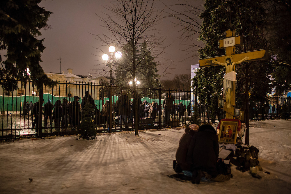 KIEV, UKRAINE - DECEMBER 12: Two women pray at a religious icon outside the Ukrainian parliament, known as the Verkhovna Rada, following a rally held by the pro-government Party of Regions in support of Ukrainian President Viktor Yanukovych on December 12, 2013 in Kiev, Ukraine. Thousands of people have been protesting against the government since a decision by President Yanukovych to suspend a trade and partnership agreement with the European Union in favor of incentives from Russia. (Photo by Brendan Hoffman/Getty Images) *** Local Caption ***