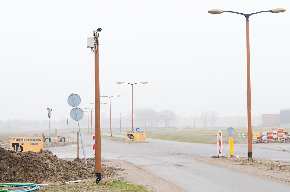 Nederland, Almelo, 20110225..Weg door het nieuwe XL Businesspark Twente langs de A35 en de A1 bij Almelo. .Weg met een eenzame boom. Op een paal een bewakingscamera..Het hele businesspark is tot stand gekomen met subsidie van Europa. ..Netherlands, Almelo, 20110225..Way through the new XL Business Twente along the A35 and the A1 at Almelo..Away with a solitary tree. A surveillance camera on a pole..The entire business park was developed with funding from Europe.? ?
