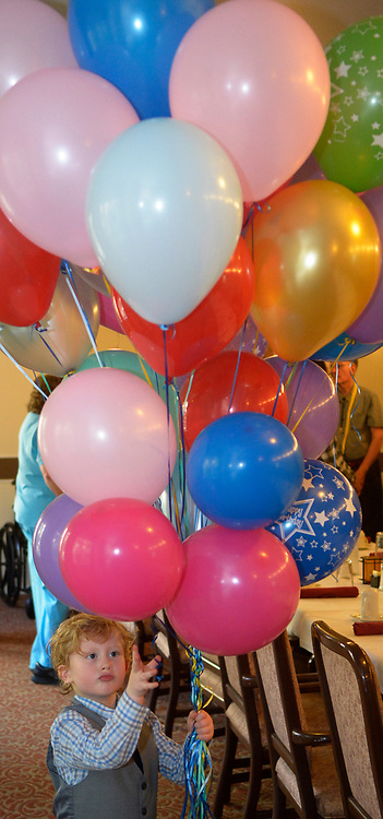 gbs072717j/LIFE  -- Rosalyn Zimmerman's great grandson Raviv Zimmerman, 4, gathers ballons during her 100th birthday party at Atria Vista del Rio assisted living facility on Thursday, July 27, 2017. (Greg Sorber/Albuquerque Journal)