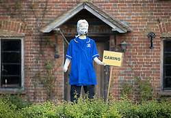 © Licensed to London News Pictures. 27/04/2020. Capel, UK. A scarecrow depiction of a care worker stands at the front of a house in the Surrey village of Capel. Residents of the village have resurrected their summer tradition of scarecrows in tribute to NHS medical staff and other key workers. Up to 30 of the life size home made doll like characters can be seen in front gardens throughout the village. The public have been told they can only leave their homes when absolutely essential, in an attempt to fight the spread of coronavirus COVID-19 disease. Photo credit: Peter Macdiarmid/LNP