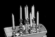Silver metal candlesticks holding unlit white candles are gathered clustered on a white-painted wooden tray.