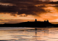 Fiery dawn breaks over Dunstanburgh Castle on the Northumberland Coast of England