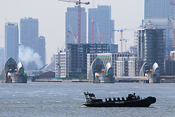 © Licensed to London News Pictures. 10/05/2017. River Police rib pictured on the Thames in an exercise at the same time a a warship deparing Canary Wharf gave off plume sof smoke. The Metropolitan Police's Marine Policing Unit pictured carrying out an exercise today on a passenger vessel in the Thames at Woolwich. The river police were seen boarding and climbing on to the Thames Clipper in the exercise by the Thames Barrier. Credit : Rob Powell/LNP