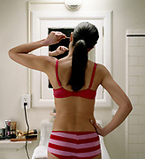 Young woman standing in front of bathroom mirror sticking swab in ear, rear view.