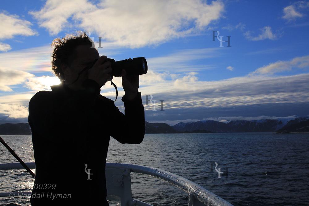 Scientist photographs mountains of Smeerenburgfjorden along northern coast of Spitsbergen island; Svalbard, Norway.