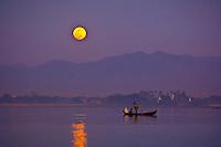 Boats crosses Taungthaman Lake, next to the U-Bein Bridge, as the moon rises, Amarapura (near Mandalay), Myanmar (Burma)