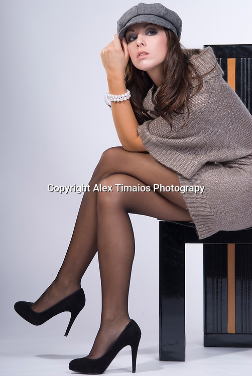 Pretty young girl with cup sitting on a designer chair