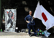 "A nationalist man holds the Japanese flag next to a poster reading ""The spirit of the samurai that changed the world/Don't forget the Greater Asia War!"" outside Yasukuni Shrine in Tokyo, Japan on 15 Aug. 2008. Wartime prime minister Hideki Tojo - who ordered the attack on Peal Harbor and was charged and hanged as a war criminal after World War II, is enshrined inside the controversial Yasukuni Shrine together with 13 other convicted war criminals, a fact that still angers citizens in China and South Korea, both of which fell vicim to Japan's wartime activities. Aug 15. is the anniversary of Japan's surrender in World War II and 100s of thousands of pilgrims from around the country visit the shrine...Photographer: Robert Gilhooly"