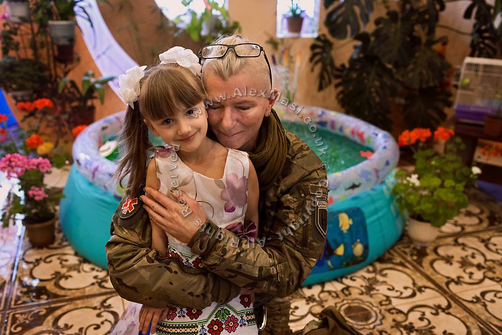 Julia Paevska is hugging a girl attending kindergarten in Myronivs'kyi, a small town near the frontline of eastern Ukraine.