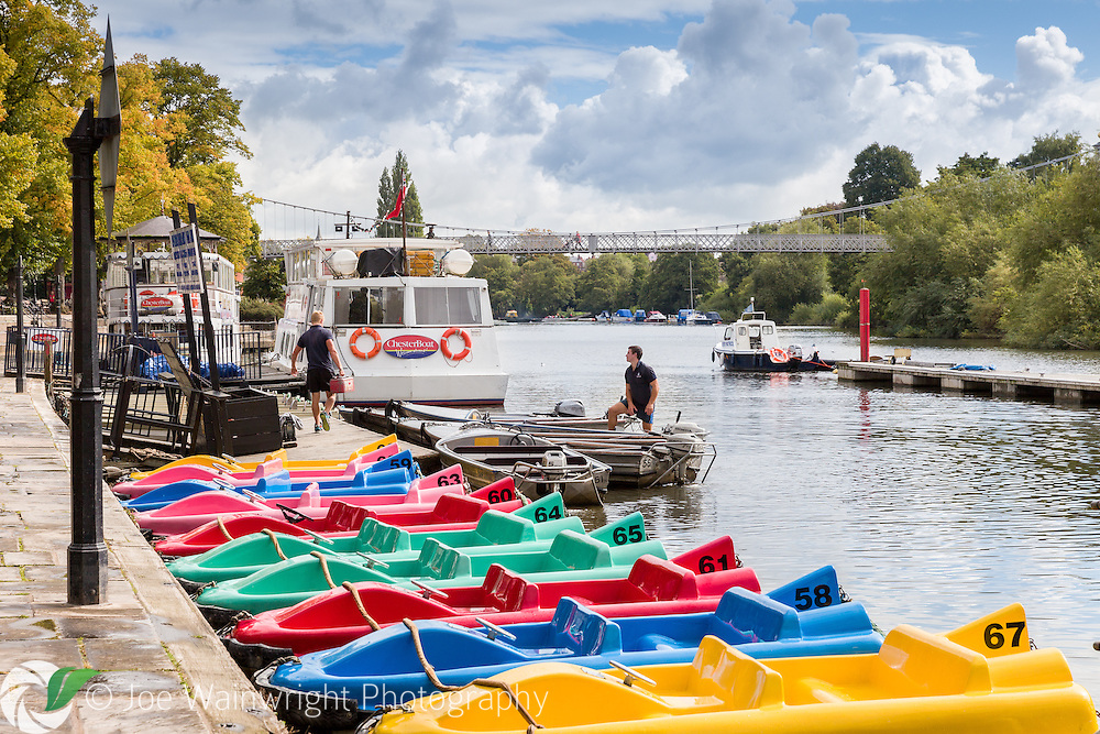 Colourful pedal boats moored on the River Dee, Chester, with the Queen's Park Suspension Bridge in the background. Photographed in August.