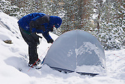 Snow falling on backpacker and tent at Gem Lake, John Muir Wilderness, Sierra Nevada Mountains, California