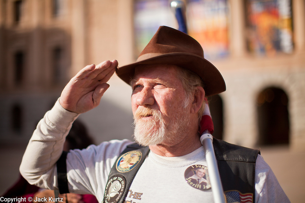 """09 JANUARY 2012 - PHOENIX, AZ:  """"Buffalo"""" Rick Galeener (CQ) salutes during the Pledge of Allegiance at the state legislature Monday. Gov Brewer delivered her State of the State inside while outside representatives of interest groups picketed and protested.    The Arizona legislature started its 2012 session and Gov. Jan Brewer delivered her State of the State Monday, Jan 9.                   PHOTO BY JACK KURTZ"""