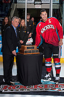 KELOWNA, CANADA - MARCH 15: WHL Commissioner Ron Robison presents Kelowna Rockets' captain Madison Bowey #4 with the Scotty Munro Memorial Trophy for the WHL regular season championship on March 15, 2014 at Prospera Place in Kelowna, British Columbia, Canada.   (Photo by Marissa Baecker/Getty Images)  *** Local Caption *** Ron Robison; Madison Bowey;