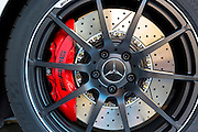 Wheel and ventilated disc brakes of AMG Mercedes SLS 6.3 showing red caliper at AMG showroom in Munich, Bavaria, Germany